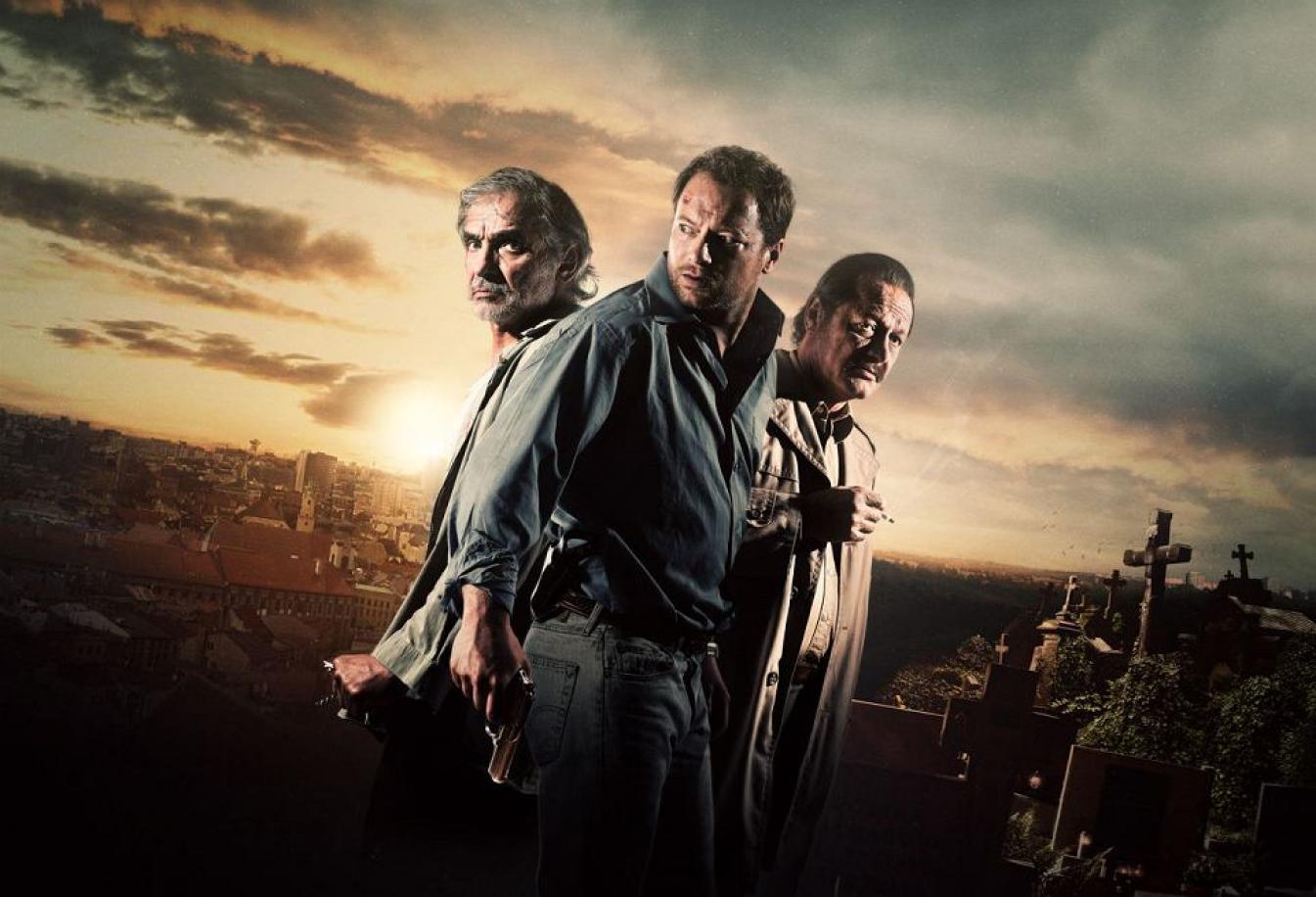Trzech mężczyzn stoi obok siebie. Mężczyzna w środku trzyma pistolet. W tle cmentarz.