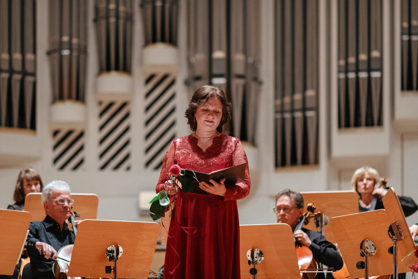 Kobieta w czerwonej sukni trzymająca w ręku różę oraz nuty na tle muzyków w filharmonii