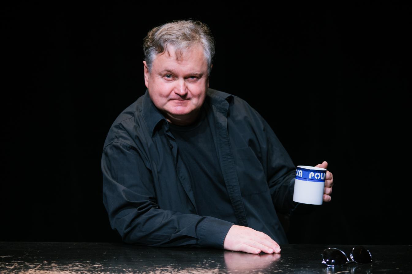 Mężczyzna siedzi przy stole, trzyma w jednej ręce kubek