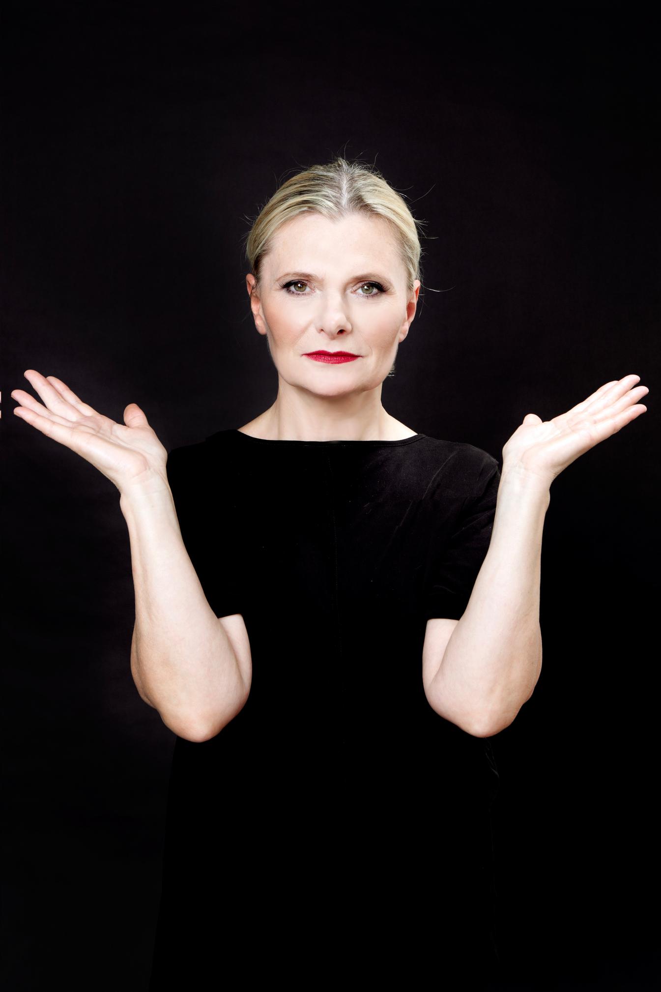 Kobieta w czarnej sukni stoi i rozkłada ręce. Patrzy przed siebie.
