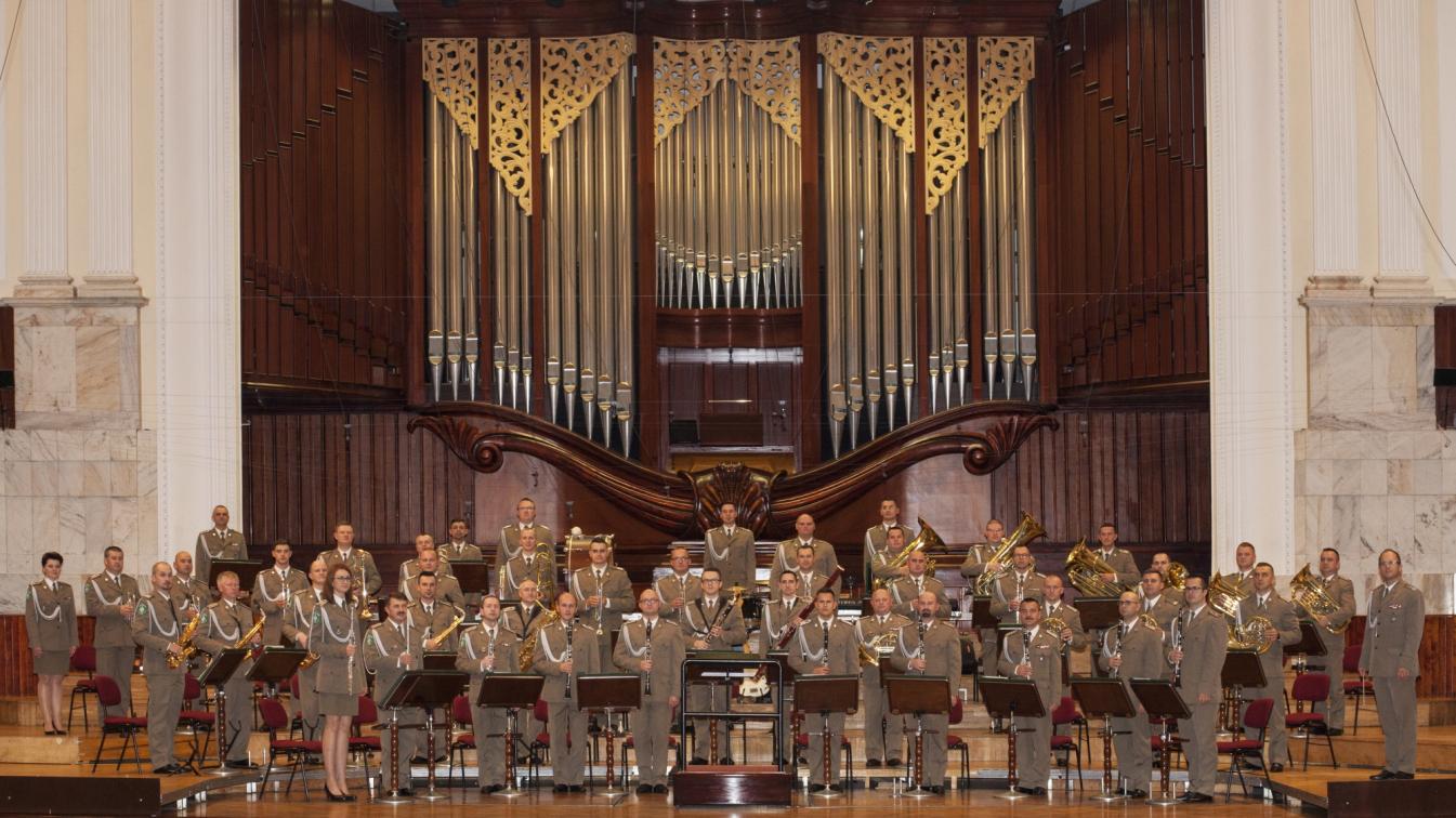 Grupa muzyków w strojach mundurowych. W tle piszczałki organowe