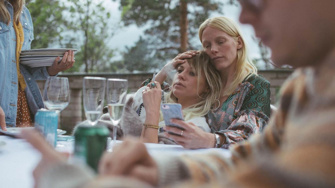Dwie kobiety siedzą przy stole. Jedna jest oparta o ramię drugiej.