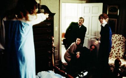 Dziewczynka stoi na łóżku i palcem wskazuje w stronę osób dorosłych stojących obok drzwi