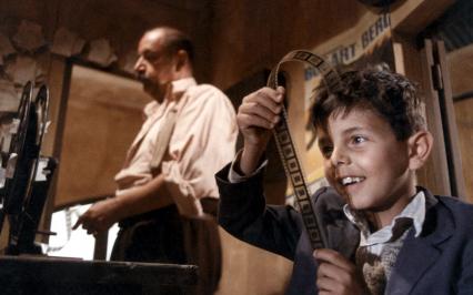 Chłopiec przygląda się kliszy filmowej, za nim stoi mężczyzna
