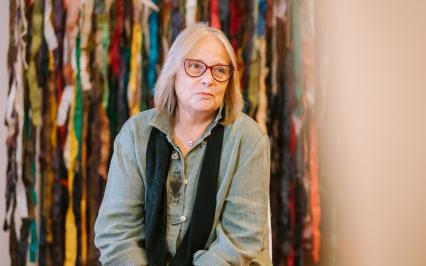 kobieta siedzi na krześle, za nią widać kolorowe strzępki papieru